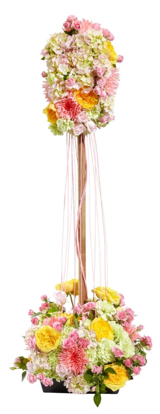 This extremely pretty arrangement reminds me of a maypole. It is built around an OASIS floral foam stake in a large square container filled with floral foam. There are 50 green carnations, 10 yellow roses, 25 sweet Akito roses 1 spray of Eileen roses