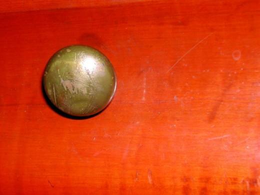 Drawer pull on center drawer.  Original brass hardware.