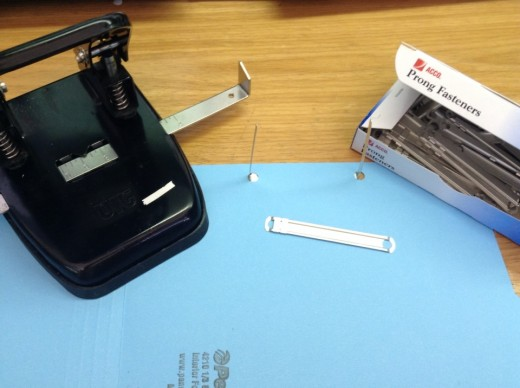 Using a two-hole punch and prong fasteners you can clip files to folders so they won't fall out when handling the folders.