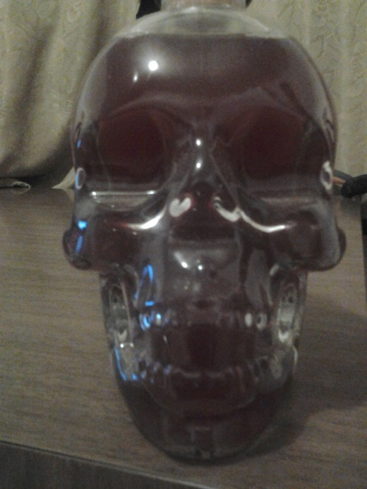 Glass skull decanter used as Halloween decoration