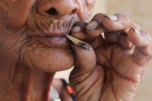 Should smoking be banned: Old woman smoking a roll up cigarette.  It has been clear since the middle of the twentieth century that smoking is hugely detrimental to health, yet the practice still remains relatively common.
