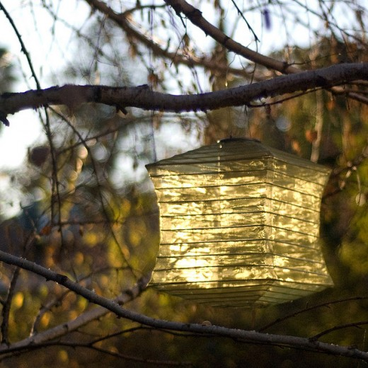 A small solar panel on top of a lantern charges a battery and runs a couple of white LEDs for a few hours after sundown