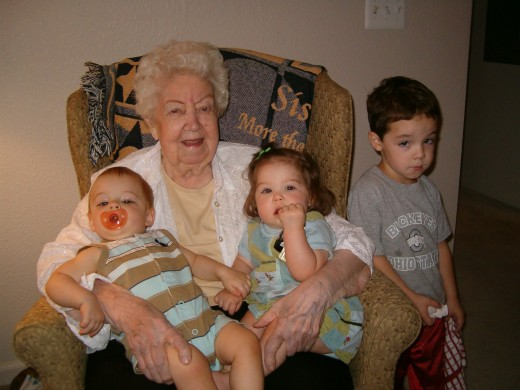 Grandmother cuddles grandchildren with great happiness.