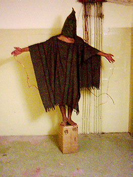 A victim of torture at Abu Ghraib prison. Note the electrical wires attached to the hands.