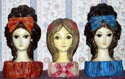 """These papier-mache lipstick holders remind me of Margaret Keane's almond-eyed women. The center holder is dated 1966, and stands 7 1/2"""" tall. The bouffant girls on each end have no markings and are almost 10"""" tall. These nifty lipstick holders were p"""