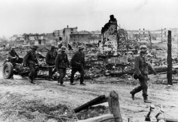 German soldiers pull a light infantry gun forward into a new position to take enemy bases under a successful fire in Stalingrad.