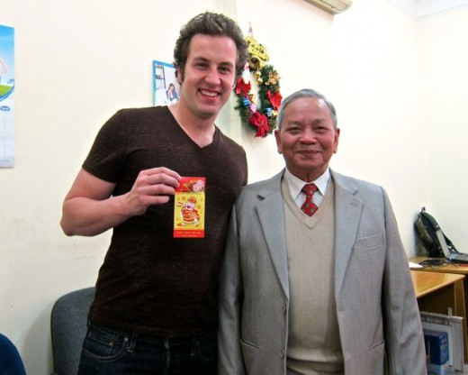 Our grandson receiving a rd envelope from our Vietnamese friend