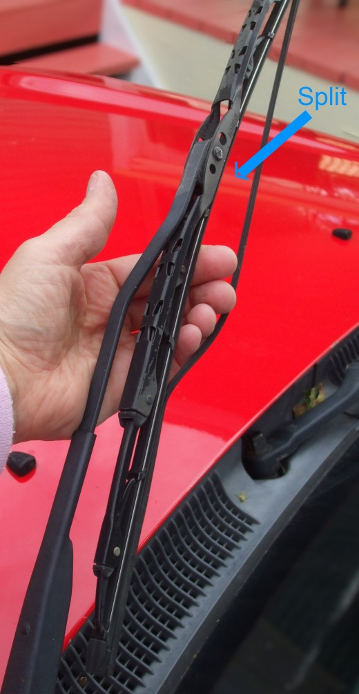 Fingers hold open the two torn parts of the rubber squeegie blade on a car windshield wiper.  There should NOT be 2 parts.