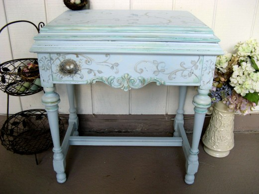 "This charmingly distressed ""shabby chic"" console table is an old sewing cabinet in disguise, hand painted in layered blue tones with verdigris patina applied to the scrollwork, with a delicate hand-painted birds nest as accent."