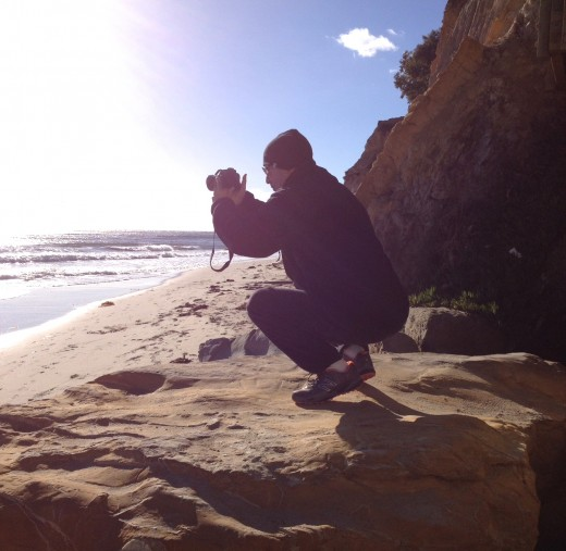 Taking photos on a big rock on the beach.