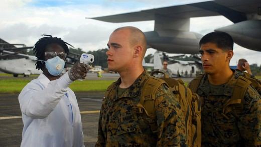 Marines from the Special Purpose Marine Air Ground Task Force getting their temperature checked as they exit a KC-130.