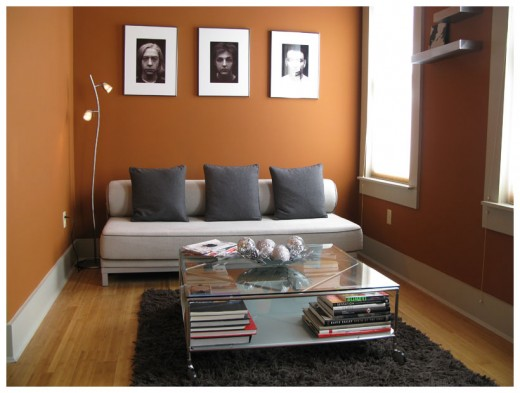 A small living room with black and white photos on the wall.