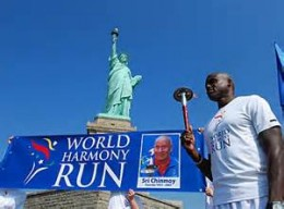 Sudahota Carl Lewis with the Sri Chinmoy Oneness-Home Peace Torch. Statue of Liberty in background.