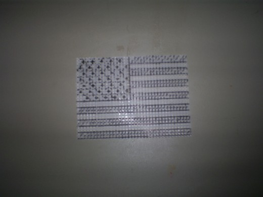 Use the grid of the plastic canvas mesh to draw out the stars and stripes of the flag.