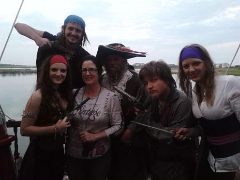 Pirates that enjoy their job and a cruise ship full of people that are captivated by the entertainment.