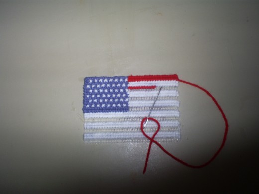 "Begin cross stitching on the red stripes of the American flag.  The red and white stripes of the American flag are in what is known as the ""field"" or ""ground"" portion of the flag."
