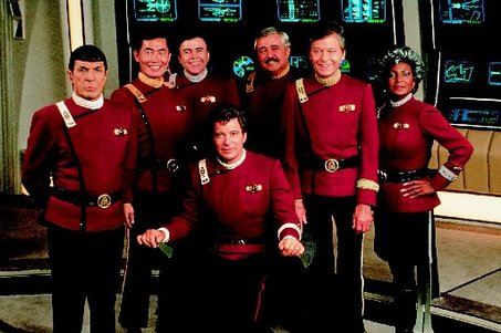 The cast of Star Trek: The Original Series on the set of Star Trek V.  From left: Leonard Nimoy, George Takei, Walter Koenig, James Doohan, DeForest Kelley, Nichelle Nichols and William Shatner (seated in front).
