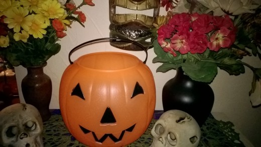 6 Halloween Party Décor Themes--Trick or Treat theme with pumpkin bucket and autumn flowers.