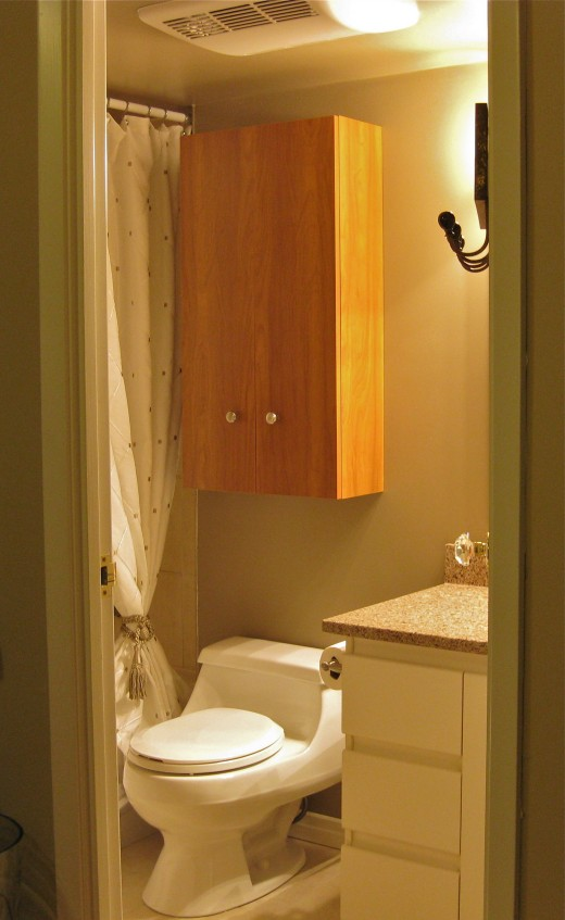Install an over-john cabinet that offers shelving closed behind doors to utilize the space above the toilet.