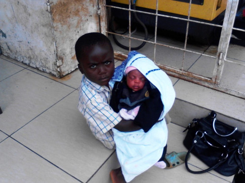 A little boy intently taking care of his sibling outside bakery in Limbe