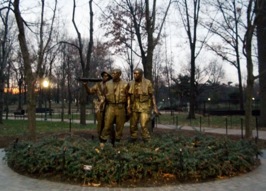 The Three Servicemen Statue is located near the entrance to the Vietnam War Memorial.