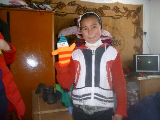 Child holding a knitted hand puppet.