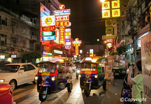 Tuk-tuks zoom along a hectic Bangkok street.
