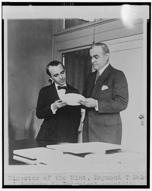 Director of the Mint, Raymond T. Baker (on the right of the photograph), and Anthony de Francisci examining model of new silver dollar.