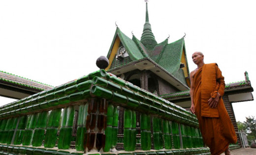 A monk standing outside The Temple of a Million Beer Bottles, in Sisaket.