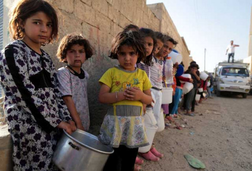 Syrian refugees waiting in a breadline for their food.