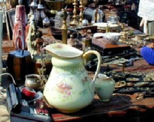 A table of items for sale at a UK antiques and collectables fair (show)