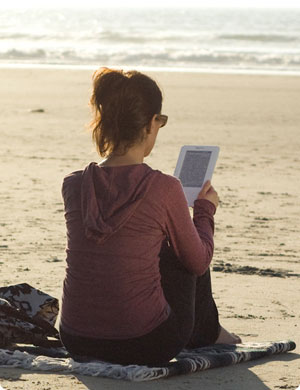 Woman Using Kindle eBook Reader at the Beach
