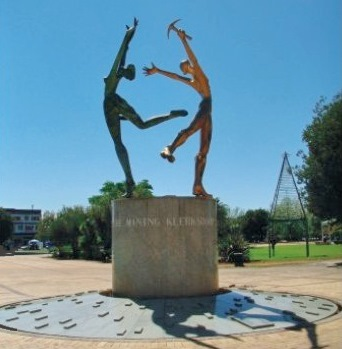 Klerksdorp's emblem: A man and a woman representing the main economy of the district - gold mining and agriculture.