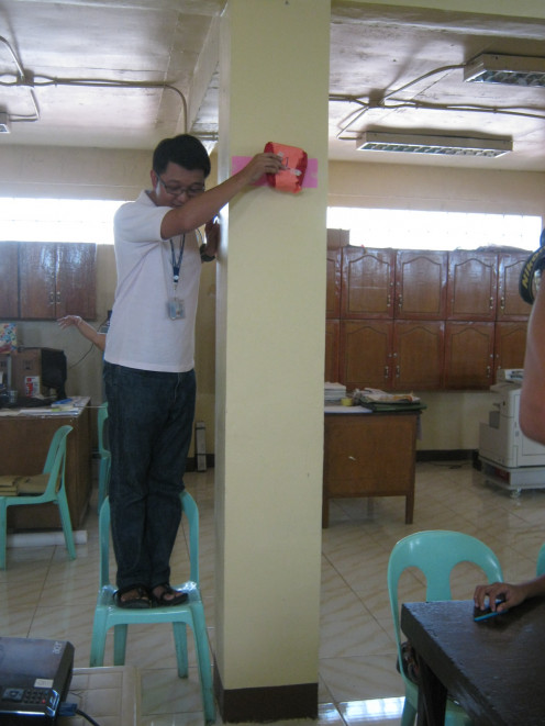 Kuya Mike as he position himself  to drop the egg 6 feet above the ground. The children are excited of the result.