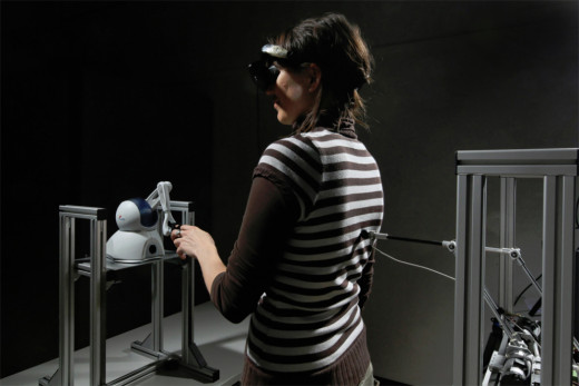 A participant interacts with the robot that helps to induce a sensation of someone standing behind them.