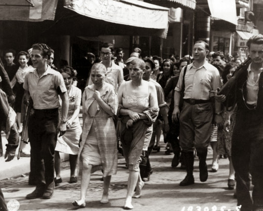 Humiliated French women, shaved, are forced to march through the streets of Paris. World War II, circa 1944