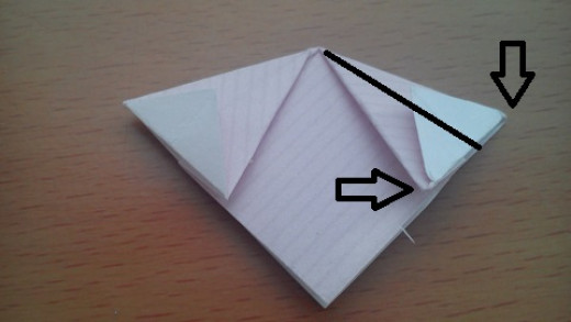 Now gently push the two edges indicated together so that the central crease pops back, and fold this back down into a diamond. See below, repeat on both sides