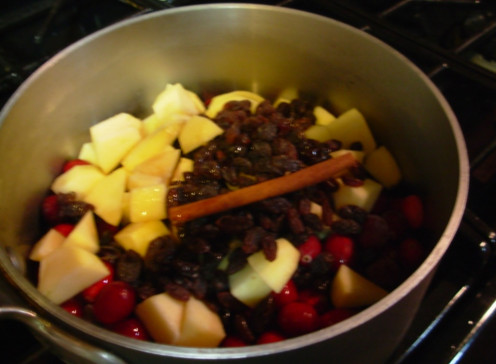 The ingredients for Apple-Cranberry Sauce are placed in a pot.