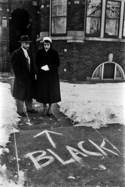 A couple who'd moved into an all-white neighborhood looks at graffiti scrawled in front of their home, Chicago, 1957 by Francis Miller