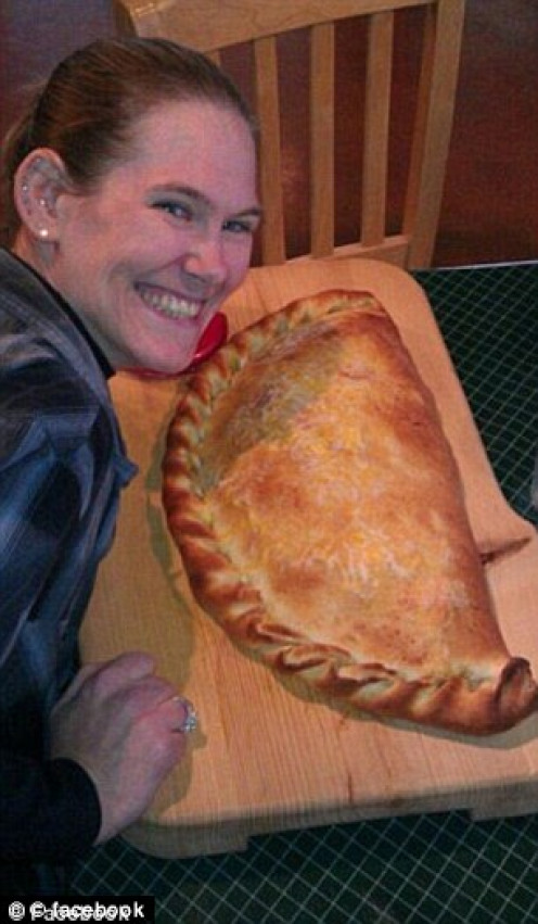 Competitive-eater, Molly Schuler, smiles over a giant pizza she is to eat