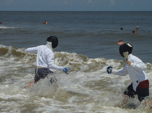 Two fencers battling it out in the surf.