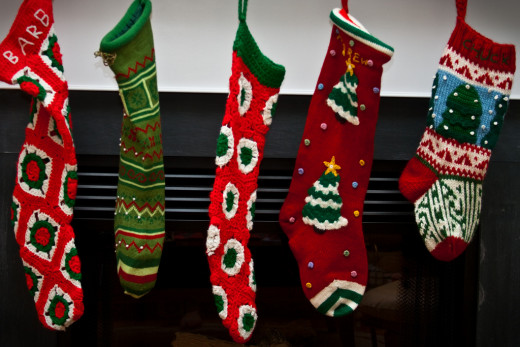 Knitted and crocheted Christmas stockings in various patterns, red and green color schemes, all hanging by the fireplace.