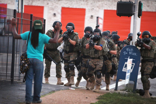 A black man holds up hands in fear, facing several heavily armed police who are pointing the barrels of their guns at him.