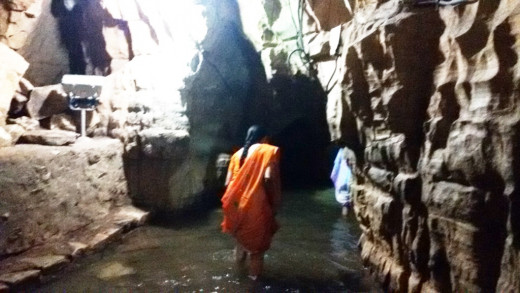 A female devotee entering the cave wading through water