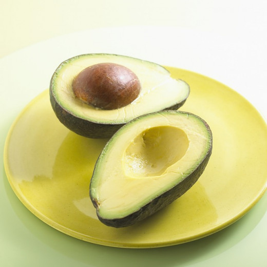Avocados are dark green on the outside, and yellow to light green on the inside. The seed is a large brown lump which is not edible. It has a rough skin but the flesh has a creamy, buttery texture.
