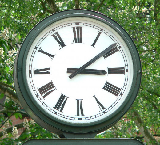 Clock with Roman numerals on the face to indicate the time.  Without even knowing the symbols we know this to show 3:09