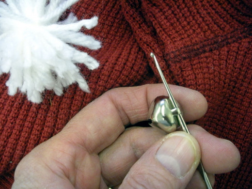 The crochet hook helps greatly with threading the yarn through the loop on the jingle bell