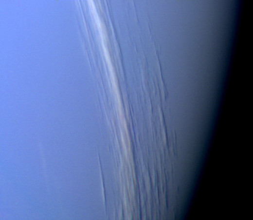 Image of Neptune showing taken by Voyager 2.  The picture shows bright cloud streaks.  The planet has very active and visible weather patterns.  It is blue thanks to the methane in the atmosphere which reflects the blue light from the Sun.