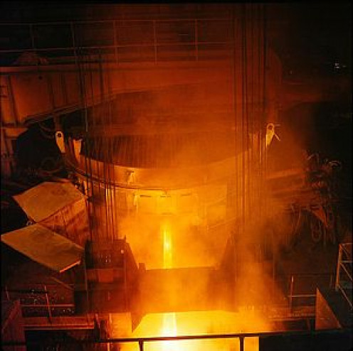 An electric arc furnace (the large cylinder) being tapped at a steel mill