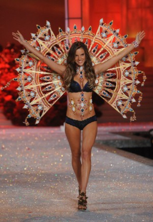 Alessandra Ambrosio wearing the heaviest pair of wings yet, a golden fan encrusted with precious gems in the 2011 VS Fashion Show.